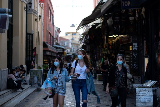 People wearing protective face masks make their way in Monastiraki square, amid the spread of the coronavirus disease (COVID-19), in Athens